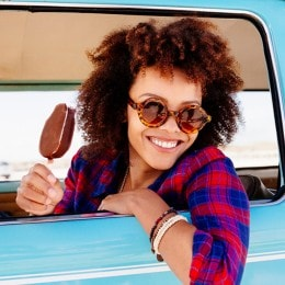 A girl with curly hair enjoying ice cream