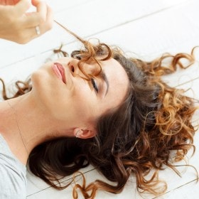 A girl lying on the ground holding a strand of her hair.
